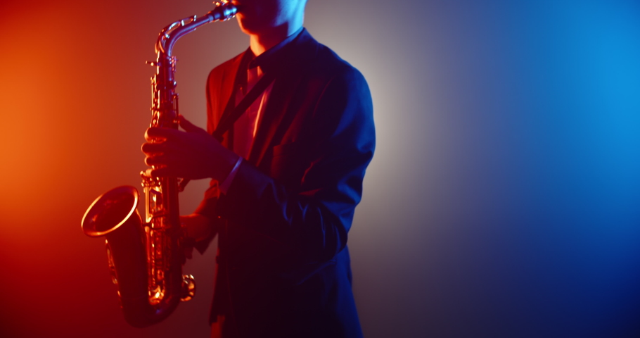 A saxophone player in suit playing a solo in jazz band, performing on red and blue lightened stage - music, art concept 4k footage   Shutterstock HD Video #1054608038