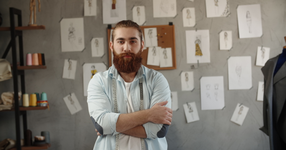 A hipster clothing designer working in his loft office, creating a new clothes collection, looking at camera and smiling - fashion, small business concept 4k footage