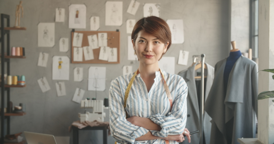 Authentic asian tailor working at her office, looking at camera and positively smiling - small business, people, success concept 4k footage portrait shot