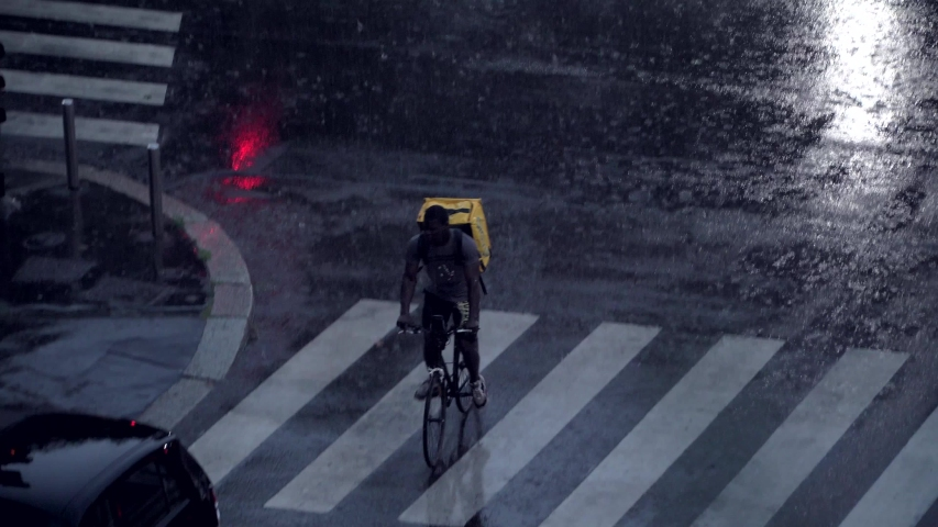 Milan, Italy. Night city in rainy weather. Cars passing on the wet asphalt of city streets. Traffic lights at night. Reflection in puddles on the ground. Crossroads at night. food delivery bike.