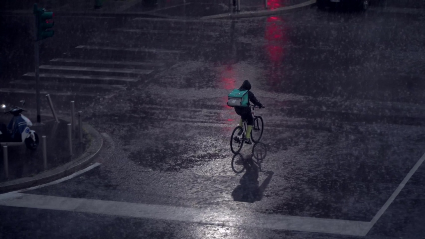 Milan, Italy. Night city in rainy weather. Cars passing on the wet asphalt of city streets. Traffic lights at night. Reflection in puddles on the ground. Crossroads at night. food delivery bike.  Royalty-Free Stock Footage #1054608122