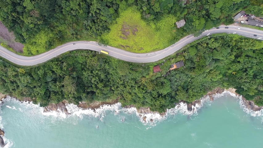 Top down view of curves of coastal road. Highway and freeway road. Beach seascape. Beach life landscape. Brazilian roads. Beach scene natural. Coastal road. Beach scene. Freeway and highway coast road | Shutterstock HD Video #1054608419