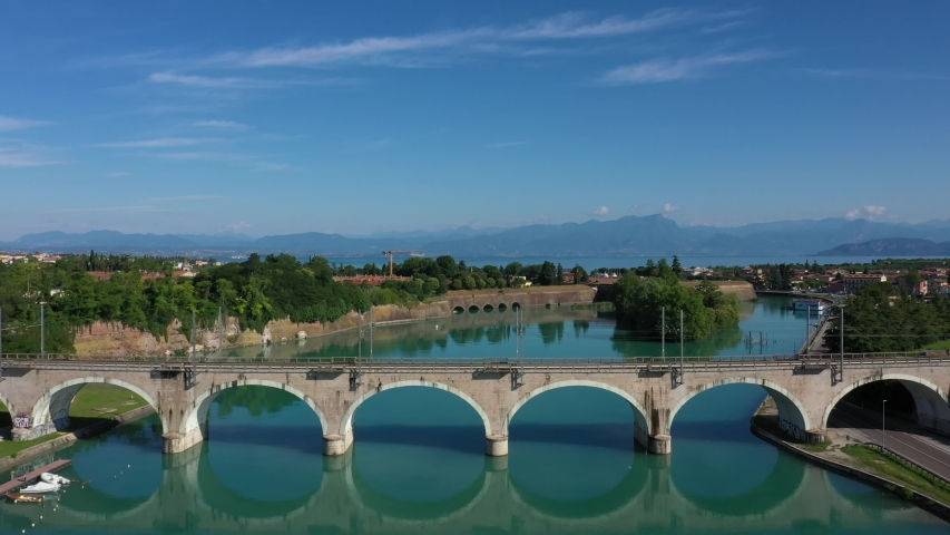 Frecciarossa high-speed train passes an arched railway bridge over a river in the background Lake Garda Italy. Red high-speed train on the bridge