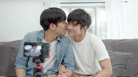 Asian couple LGBTQI blogger or vlogger looking at camera and kissing. Social media influencer people or content maker concept in relax casual style at home. LGBT relationship interview pride month.