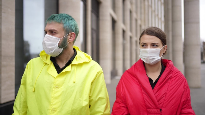 Man and woman remove protective masks in the street | Shutterstock HD Video #1054614914