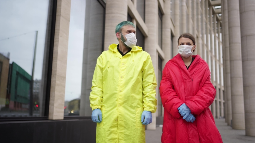 Man and woman remove protective masks in the street | Shutterstock HD Video #1054614917