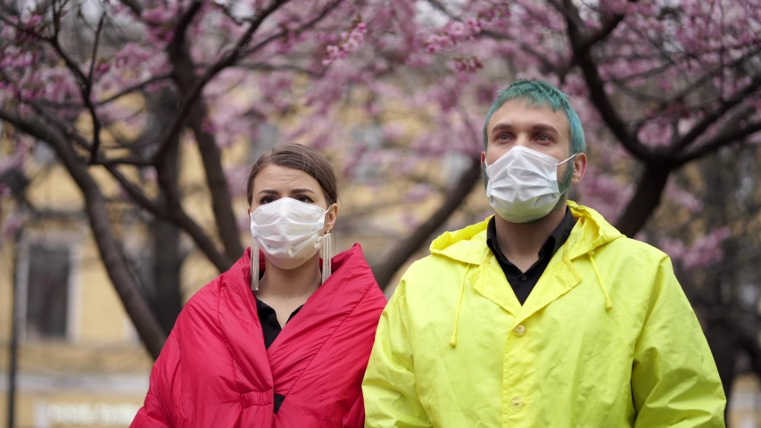 Man and woman remove protective masks in the street | Shutterstock HD Video #1054614923