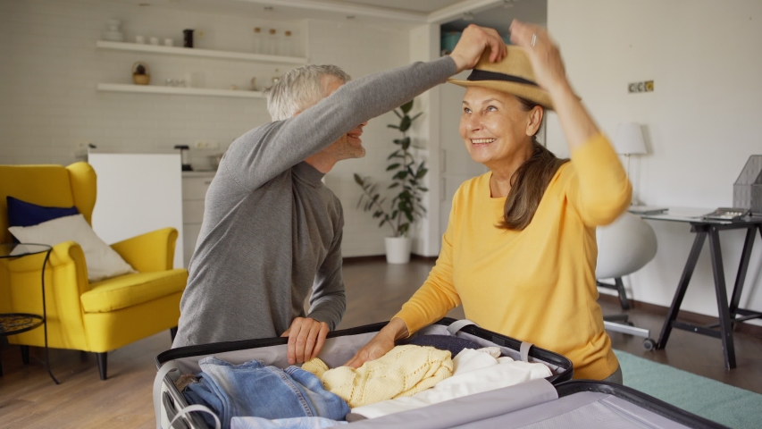 Tilt up medium shot of excited senior couple talking cheerfully while packing suitcase for vacations together. Joyful woman trying on straw hat. Happy couple closing bag and embracing