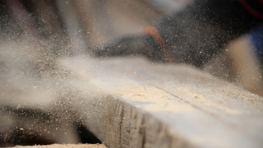 Close-up view of thick board from which sawdust is blown away from sawing with an electric circular machine. Man in working gloves blows off sawdust from a piece of wood after being cut by a grinder. | Shutterstock HD Video #1054617338