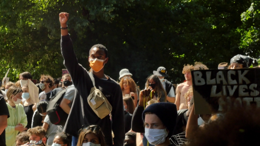 Brighton, United Kingdom - Jun 13, 2020: black protester man with clenched raised fist among thousands of protesters. BLM protest. No social distancing. Mask on. 4K