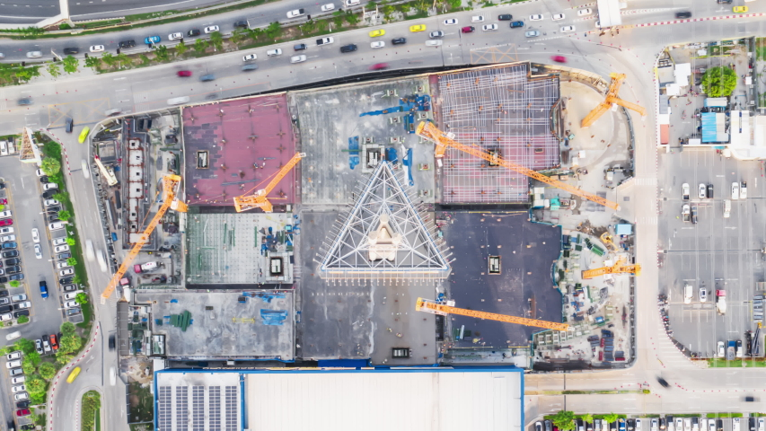 4K time-lapse of under construction site, crane, parking lot, car traffic transportation in Asian city. Drone aerial top view. Industrial business or civil engineering technology concept. Zoom out Royalty-Free Stock Footage #1054620080