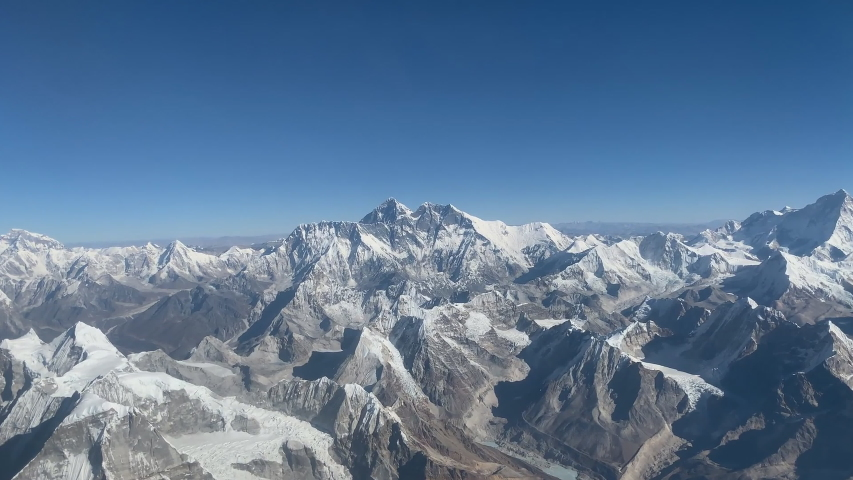 View from the plane to the surface of the earth with a mountain landscape of the Himalayas, view of Mount Everest.
