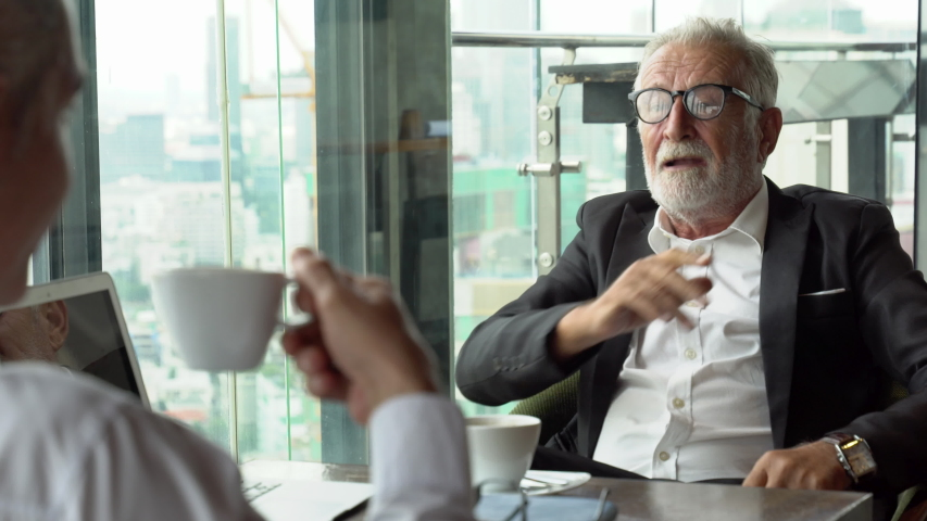 Senior businessman listening and consulting to partner disagree to idea. old man ceo discussing with client in  meeting at cafe . mature manager with coffee  talking by window over cityscape luxury