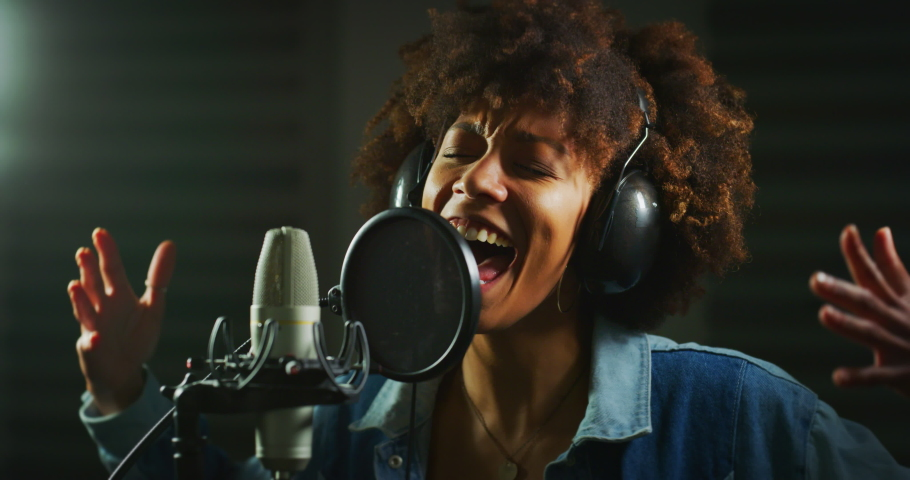 An young professional african female singer is performing a new song with a microphone while recording it in a music studio.  Royalty-Free Stock Footage #1054633739