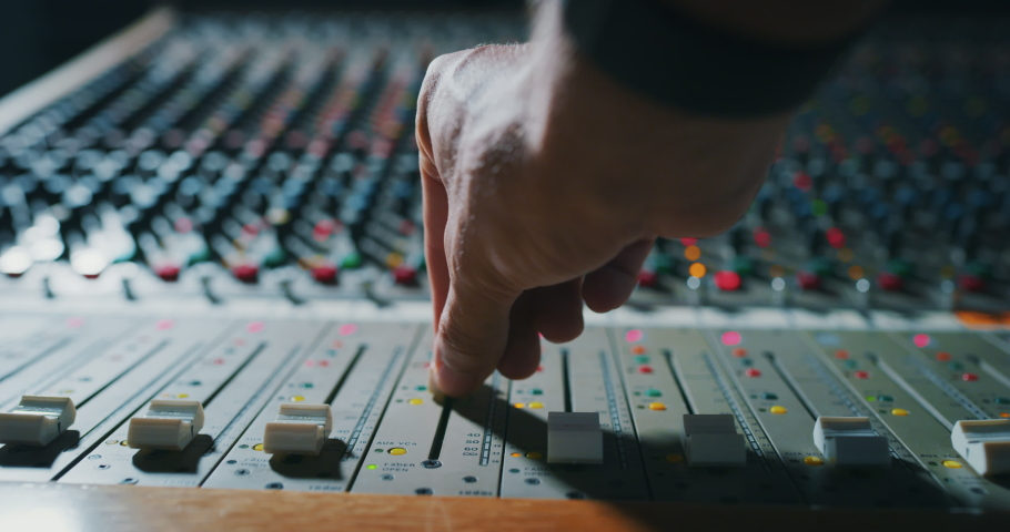 Macro slide shot of a sound producer hand is using a music mixer with editing tools in a professional recording studio.