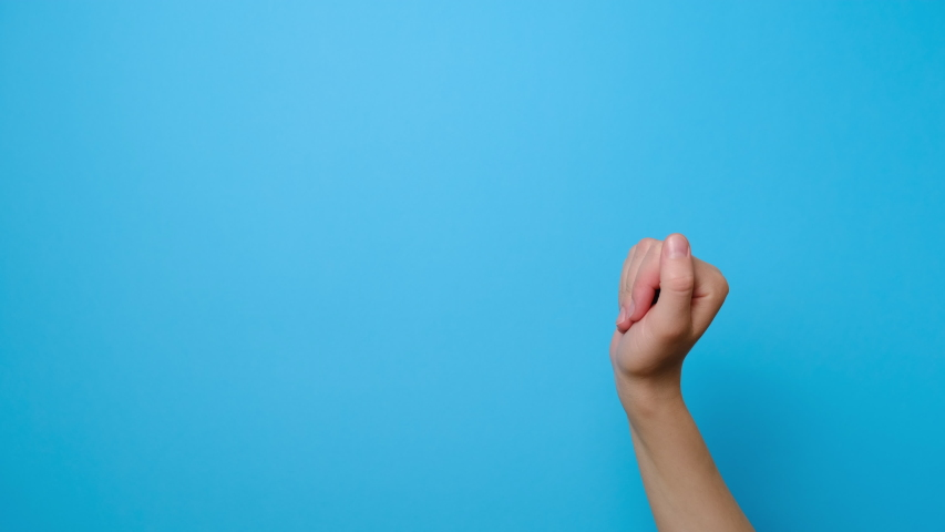 Bye gesture. Close up of unrecognizable young woman bending hand fingers fast isolated on blue studio background with copy space for advertisement. Farewell sign.