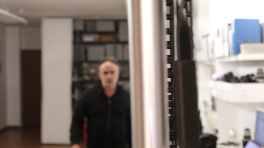 Fifty-year-old man walks into his office facing the window seriously