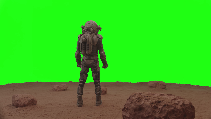 GREEN SCREEN CHROMA KEY Back view of astronaut walking on a surface of a red planet, cheking his HUD