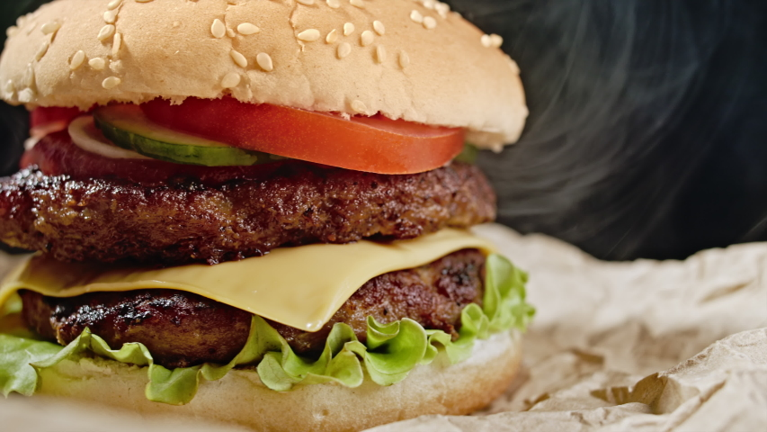 Yummy hamburger, fast food concept. Fresh homemade grilled burger with meat patty, tomatoes, cucumber, lettuce, onion and sesame seeds. Unhealthy lifestyle. Food background. 4k | Shutterstock HD Video #1054648547