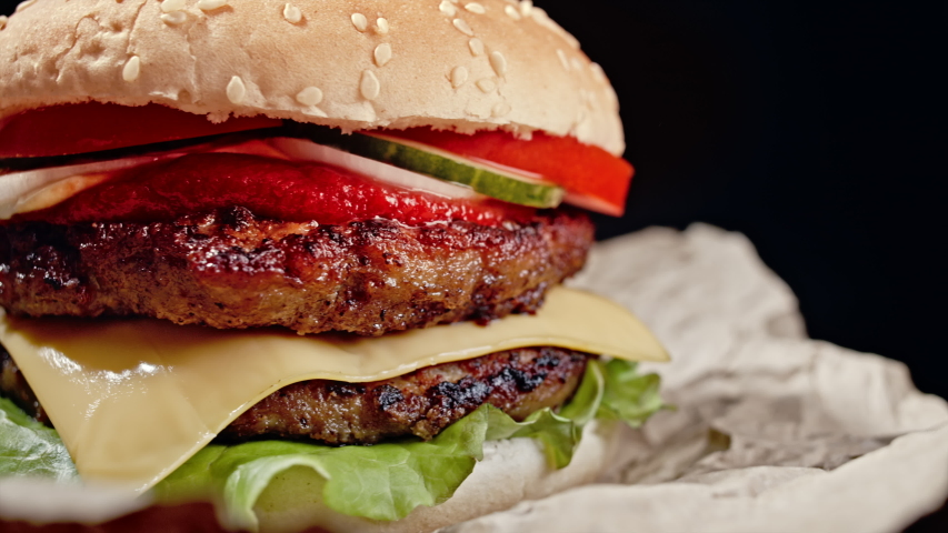 Yummy hamburger, fast food concept. Fresh homemade grilled burger with meat patty, tomatoes, cucumber, lettuce, onion and sesame seeds. Unhealthy lifestyle. Food background. 4k Royalty-Free Stock Footage #1054648550