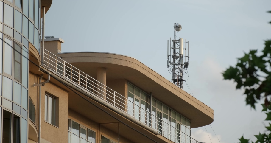 Telecommunication tower near building. Telecom tower antennas and satellite transmits the signals of cellular 5g 4g mobile signals to the consumers and smartphones. 4k. 60fps fps | Shutterstock HD Video #1054658429