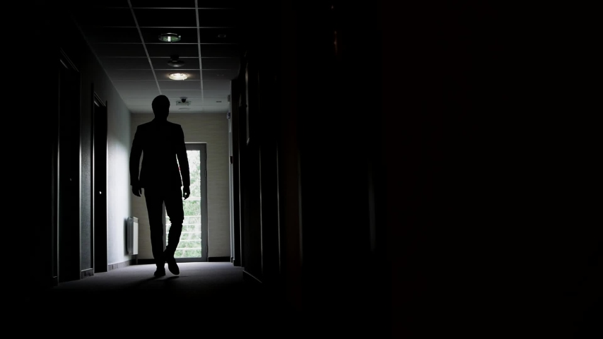 Slow motion, a backlit man walks along the corridor of an office or hotel to the glass doors, then stops and waits. | Shutterstock HD Video #1054661042