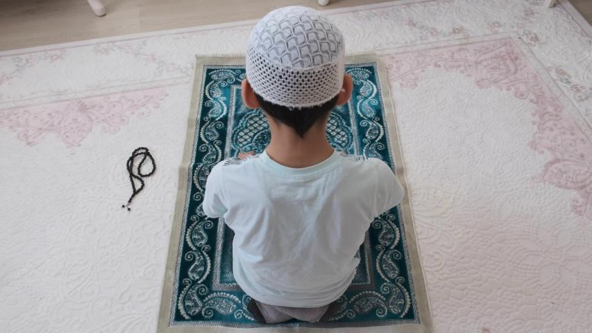 A young muslim boy praying, small young muslim is praying, | Shutterstock HD Video #1054663073