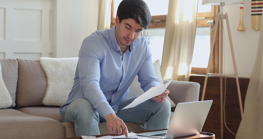 Concentrated young handsome man doing financial paperwork at home. Focused millennial guy calculating domestic monthly budget, managing incomes and outcomes, accounting taxes, bills or payments.   Shutterstock HD Video #1054663430