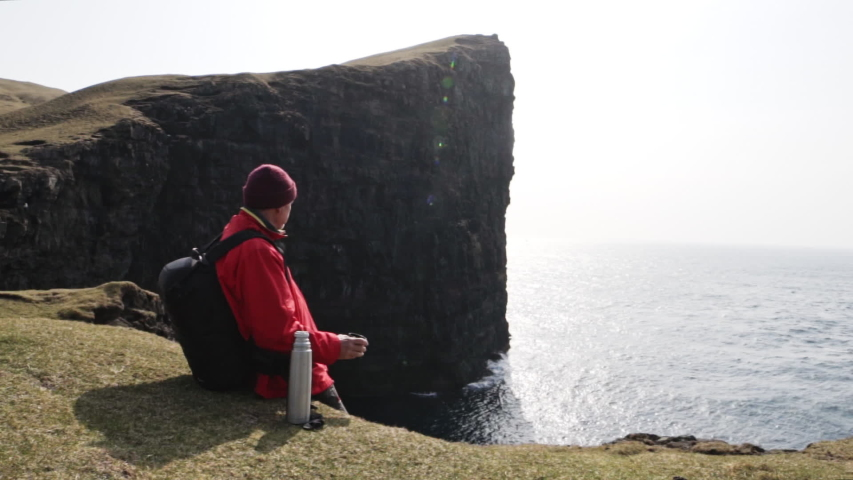 Steady shot of a man in red jacket, maroon bonnet and black backpack as he sits by the edge of the cliff overlooking ocena waters in Faroe Island