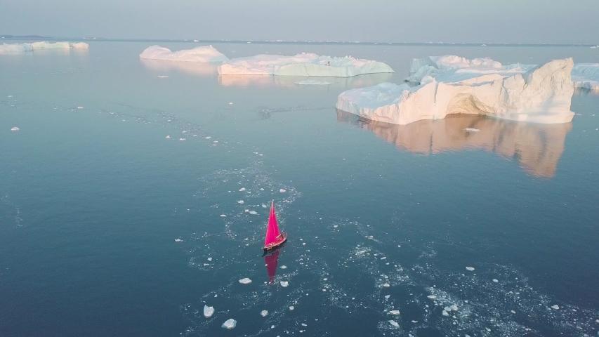 Little red sailboat cruising among floating icebergs in Disko Bay glacier during midnight sun season of polar summer. Ilulissat, Greenland. Studying of a phenomenon of global warming. Unesco world   Shutterstock HD Video #1054669430