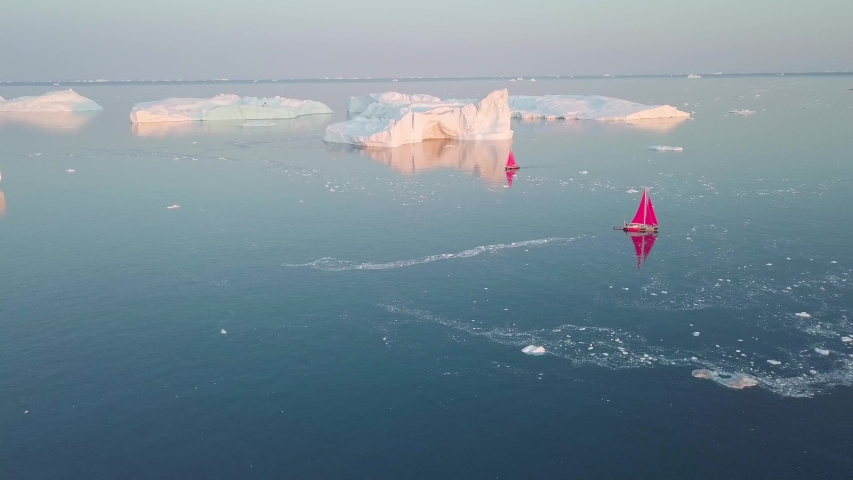 Little red sailboat cruising among floating icebergs in Disko Bay glacier during midnight sun season of polar summer. Ilulissat, Greenland. Studying of a phenomenon of global warming. Unesco world   Shutterstock HD Video #1054669436