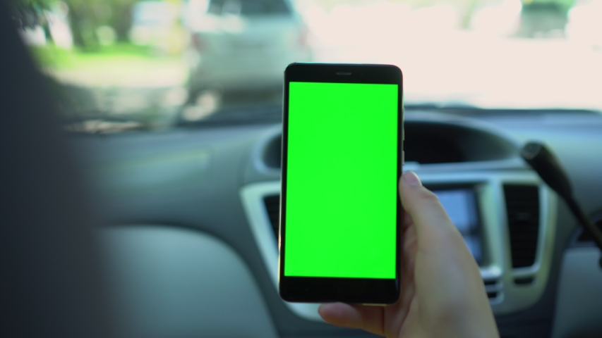 Close up of a woman's hand holding a mobile telephone with a vertical green screen in car chroma key smartphone technology cell phone street touch message display hand | Shutterstock HD Video #1054669553
