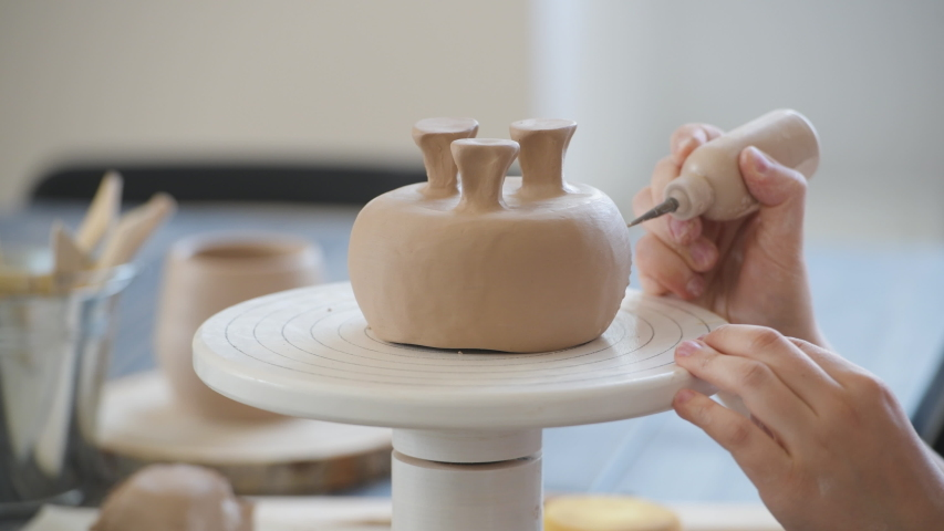 Child in the process of decorating the clay vase. Children pottery studio. | Shutterstock HD Video #1054670531