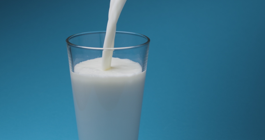 Milk is poured into a milk glass on a blue background. | Shutterstock HD Video #1054671335
