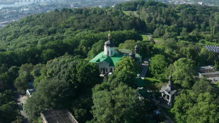 Holy Trinity Ioninsky Monastery of the Ukrainian Orthodox Church. Orbiting Panorama Drone Shot of Monastery with a copper roof and a golden cross in the morning among the summer green trees.
