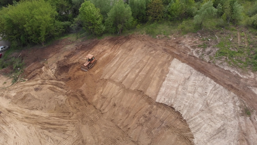 Aerial view of bulldozer flattening surface on further construction site. 4K   Shutterstock HD Video #1054673366