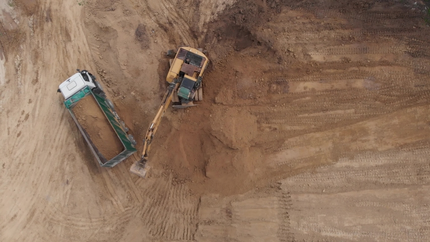 Aerial top view: yellow excavator pouring soil into tipper. Preparing place to construction residential house. 4K   Shutterstock HD Video #1054673369