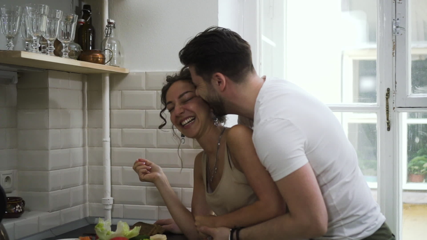 cheerful mature couple hugging flirting in kitchen having romantic relationship Sbbd. wife and husband embrace share intimate connection. enjoying happy lifestyle together Royalty-Free Stock Footage #1054674059