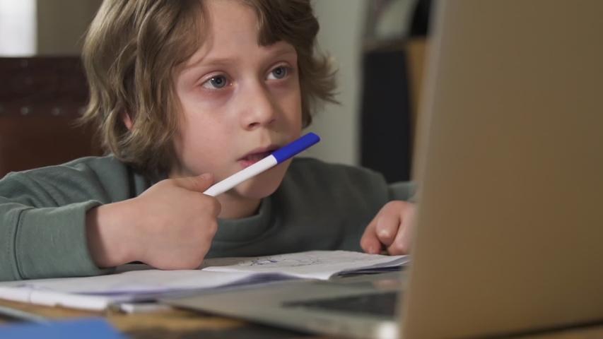 Schoolboy pupil talking to internet teacher via laptop Spbd. discuss homework through online education. young boy student kid e-learning with tutor on quarantine   Shutterstock HD Video #1054674113