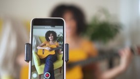 young woman at home singing and playing guitar for followers Spbd. filming blog about learning to sing popular songs. cover, smartphone, recording. confident singer performer