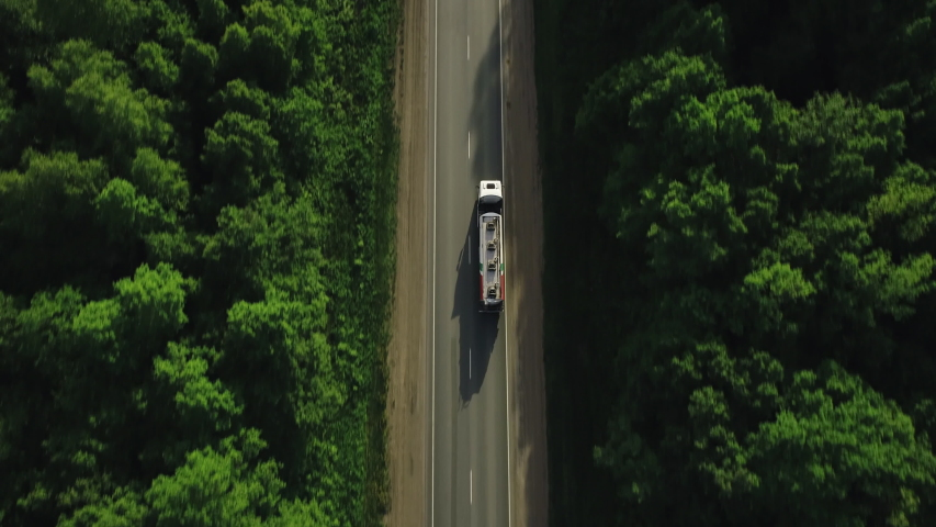 Gasoline tanker truck on asphalt road / White fuel semi truck fast driving on straight freeway in countryside dense forest at summer sunset / Aerial top down drone follow shot