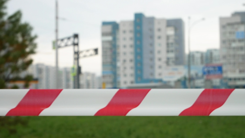 A barrier tape fluttering in the wind against the city buildings background | Shutterstock HD Video #1054674260