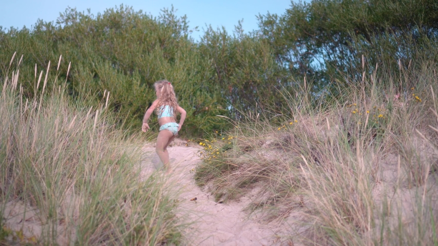 Five years old blonde girl in swimsuit walking barefoot on top of the dune. Camera motion shot with gimbal. | Shutterstock HD Video #1054674476
