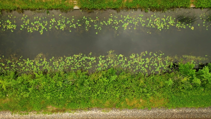 Top-down view over the Royal Canal, Co.Kilkenny, Ireland.  Aerial view over rural Ireland and fishing canal. Drone zooms out revealing the train tracks and walking pathway.   Shutterstock HD Video #1054674491
