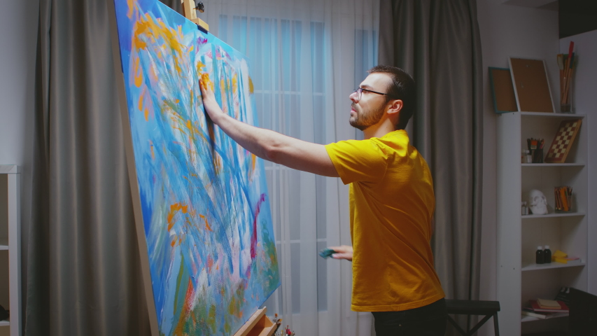Successful painter using his hands to creat an oil painting masterpiece in art studio. Modern artwork paint on canvas, creative, contemporary and successful fine art artist drawing masterpiece
