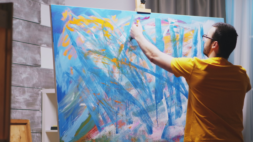 Guy painting with fingers on large canvas in art studio. Modern artwork paint on canvas, creative, contemporary and successful fine art artist drawing masterpiece
