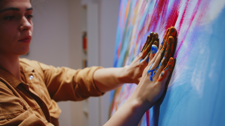 Close up of painting with fingers on large canvas in art studio. Modern artwork paint on canvas, creative, contemporary and successful fine art artist drawing masterpiece