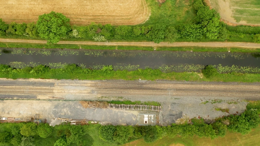 Top-down view over the Royal Canal, Co.Kilkenny, Ireland.  Aerial view over rural Ireland and fishing canal. Drone tracking left along the  train tracks and walking pathway.   Shutterstock HD Video #1054674641