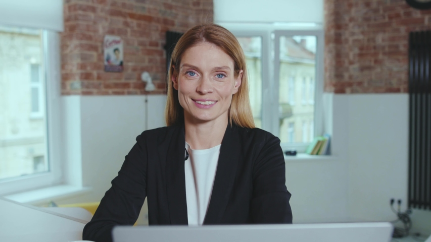 Happy attractive young business woman looking at camera smiling successful entrepreneur portrait at home office close up slow motion