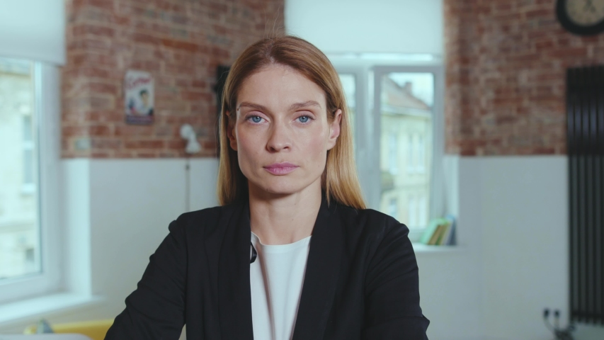 Portrait confident young attractive business woman looking at camera serious successful entrepreneur beautiful at home office close up slow motion